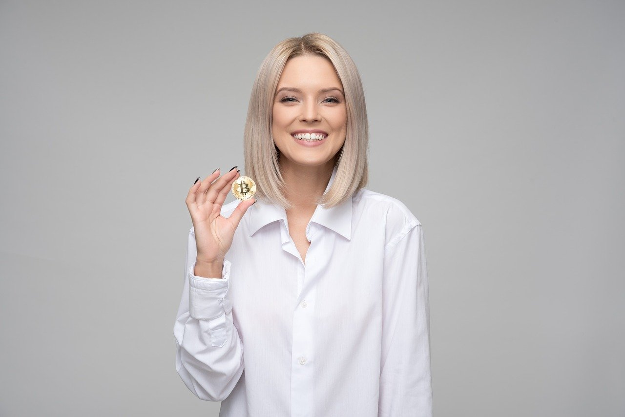 kobieta w białej koszuli z monetą w ręku